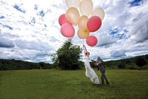Tim and Kelley floating away on wedding balloons Edges Photography
